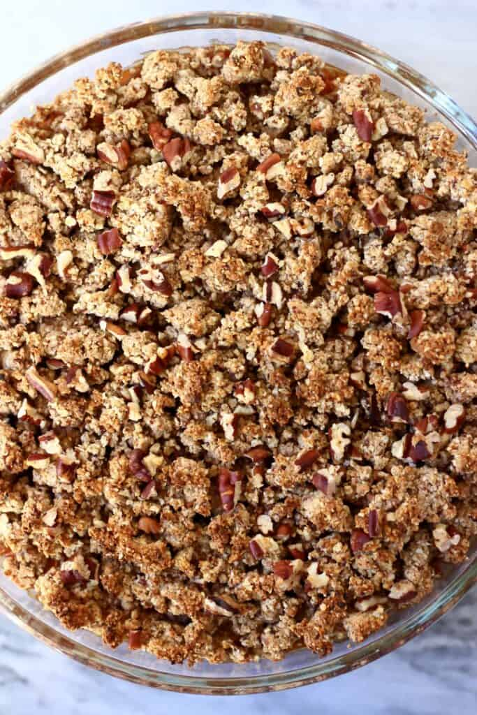 Photo of an apple crumble topped with chopped pecan nuts in a glass dish against a marble background