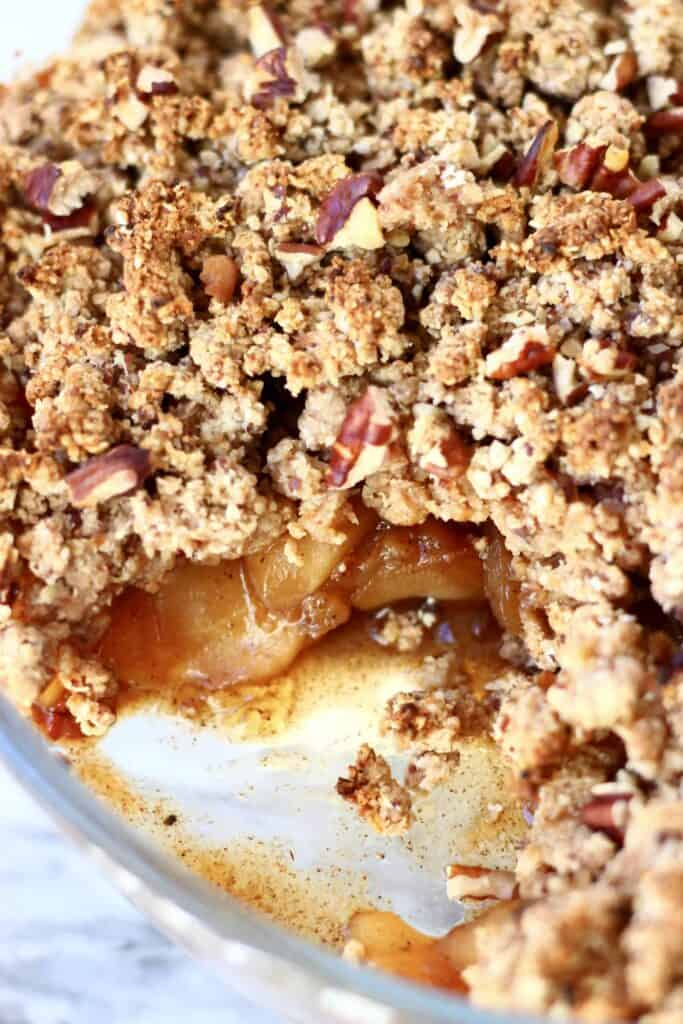 Photo of an apple crumble with a portion taken out of it in a glass dish against a marble background