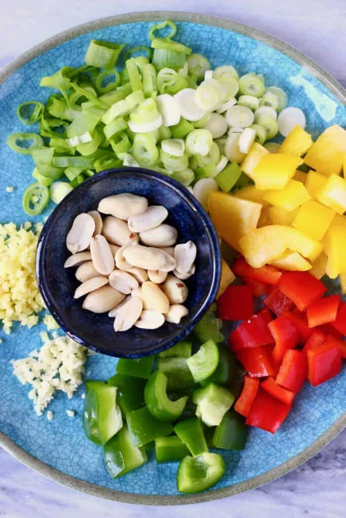 Photo of chopped vegetables and a bowl of roasted peanuts on a blue plate against a marble background