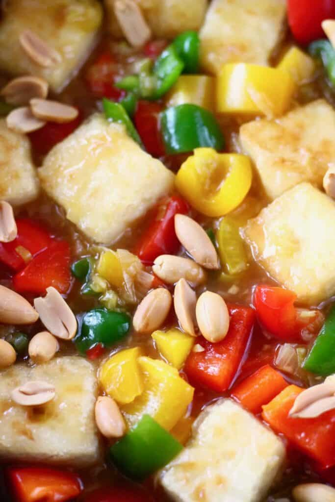 Photo of tofu cubes, peppers and peanuts in a frying pan
