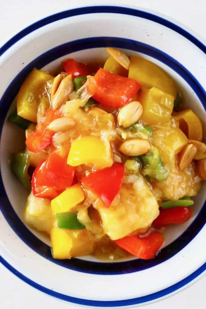 Photo of tofu cubes, peppers and peanuts in a white bowl with a blue rim
