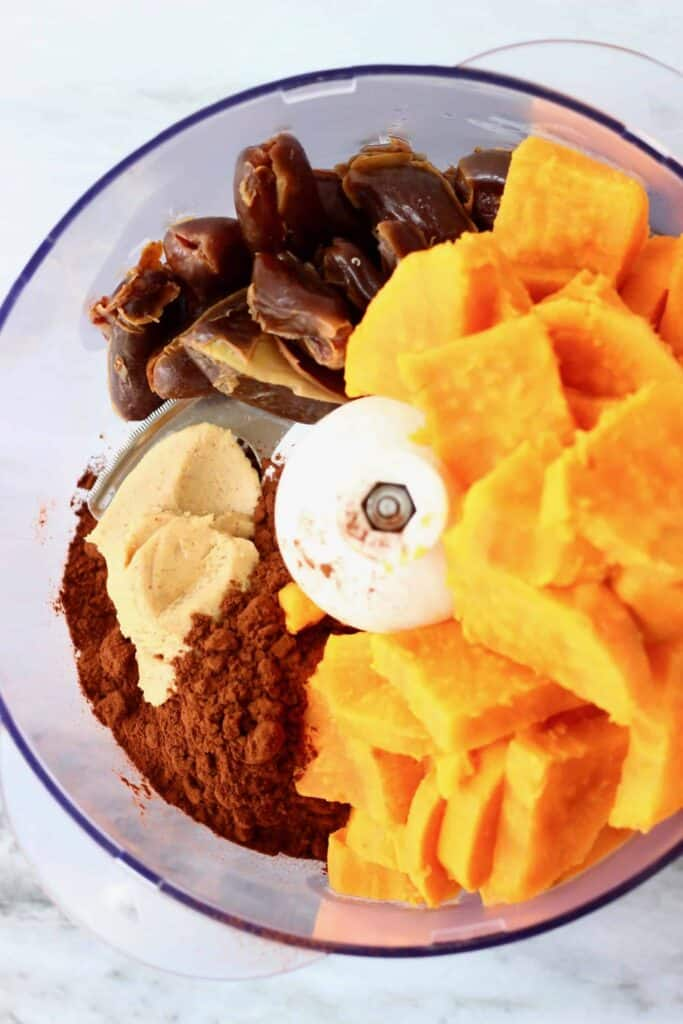 Photo of cooked orange sweet potato, dates, peanut butter and cocoa powder in a food processor against a marble background