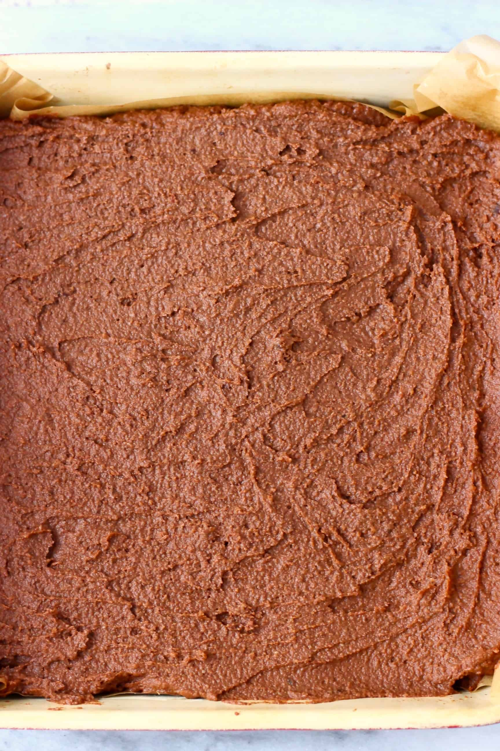 Raw sweet potato brownie batter in a baking tin lined with baking paper