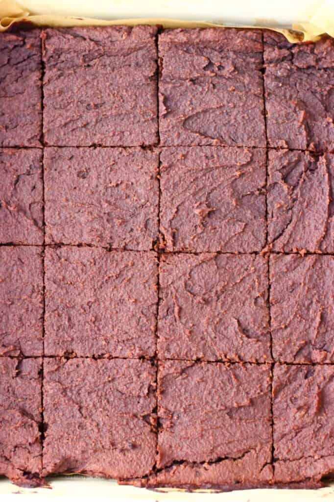 Photo of a square baking tray lined with brown baking paper with chocolate brownies cut into squares