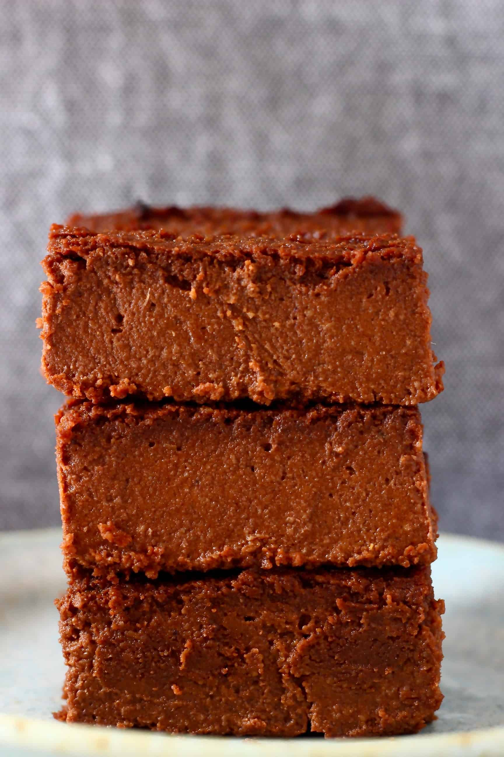 Three sweet potato brownies stacked on top of each other on a plate