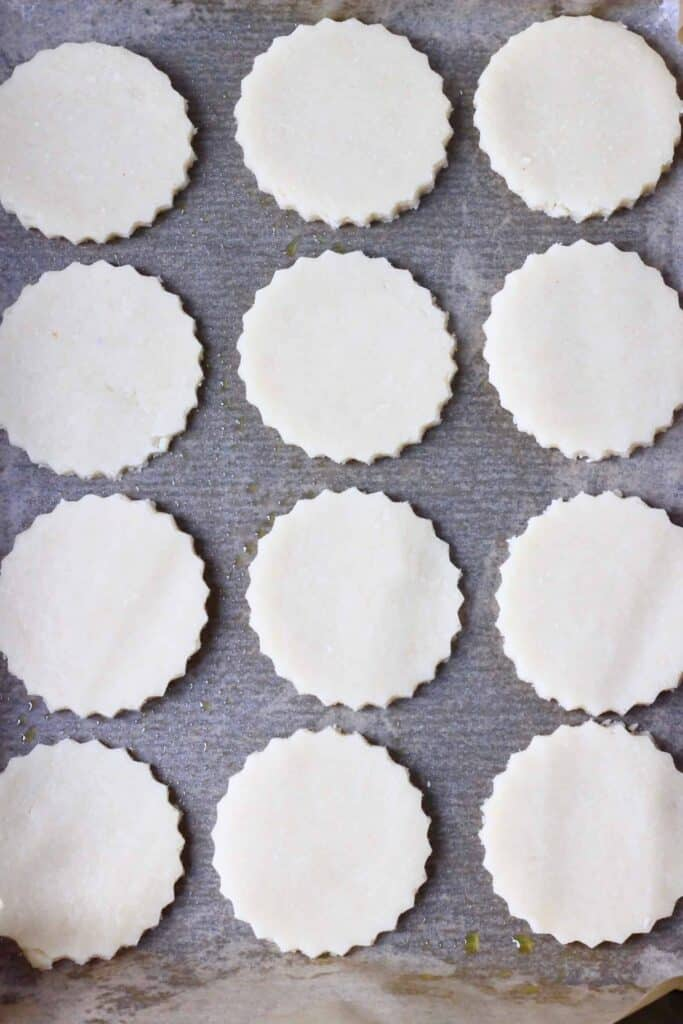 Photo of twelve circular raw cookies on a sheet of brown baking paper