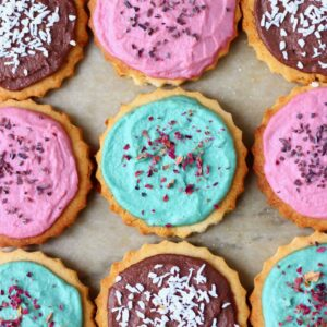 Photo of nine circular cookies topped with different coloured frosting and sprinkles on a sheet of brown baking paper