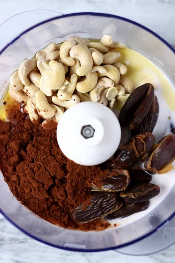 Photo of cashew nuts, dates, cocoa powder and milk in a food processor against a marble background