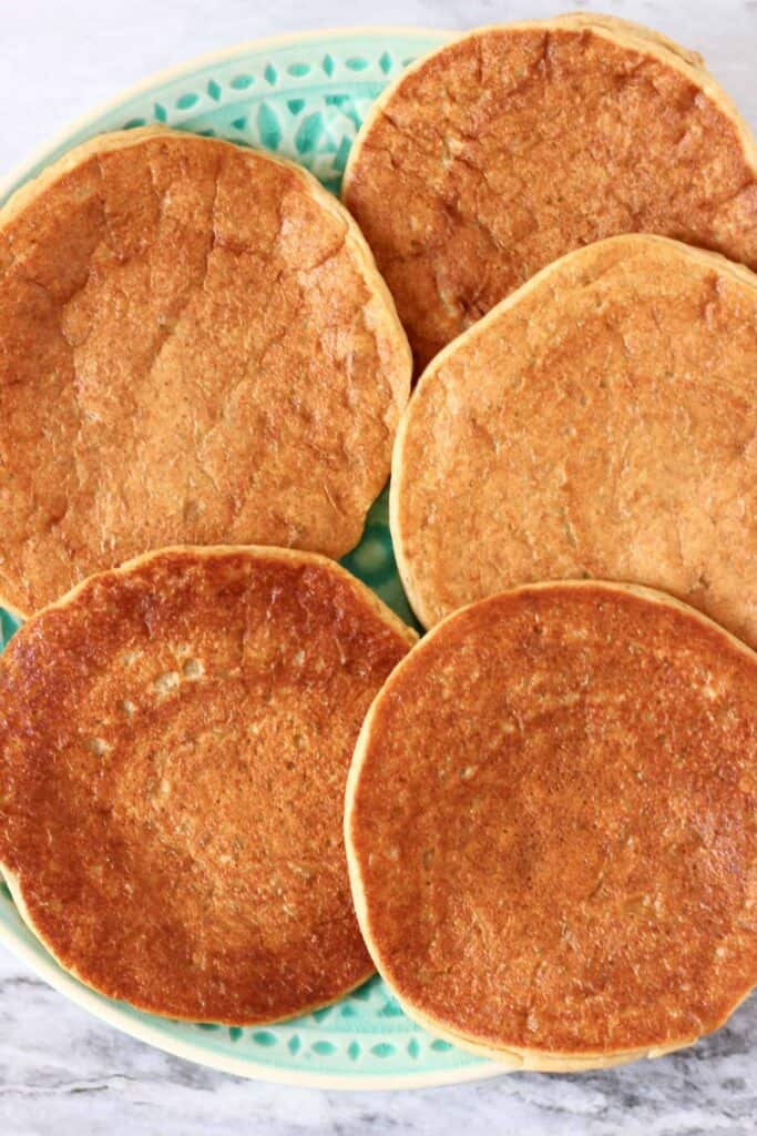 Photo of five golden brown pancakes on a green plate against a marble background