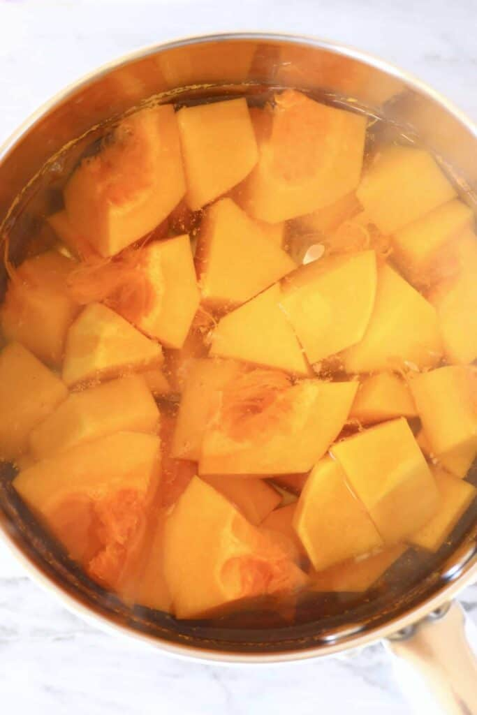 Pieces of butternut squash being boiled in a silver saucepan against a marble background