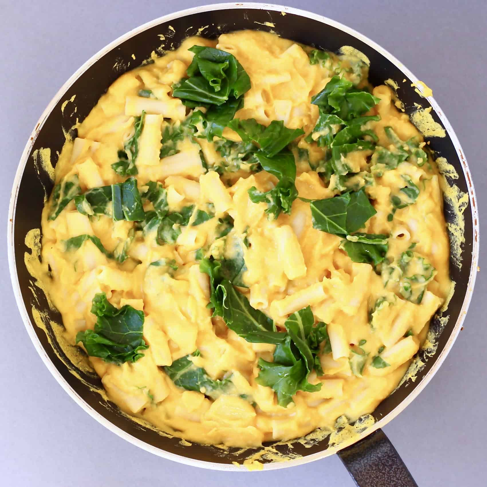 Photo of pasta with orange butternut squash sauce and green kale in a black frying pan against a grey background