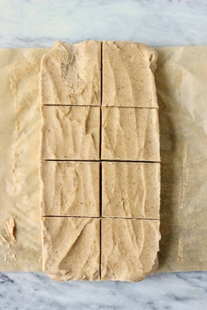 Photo of eight squares of fudge on a sheet of brown baking paper against a marble background