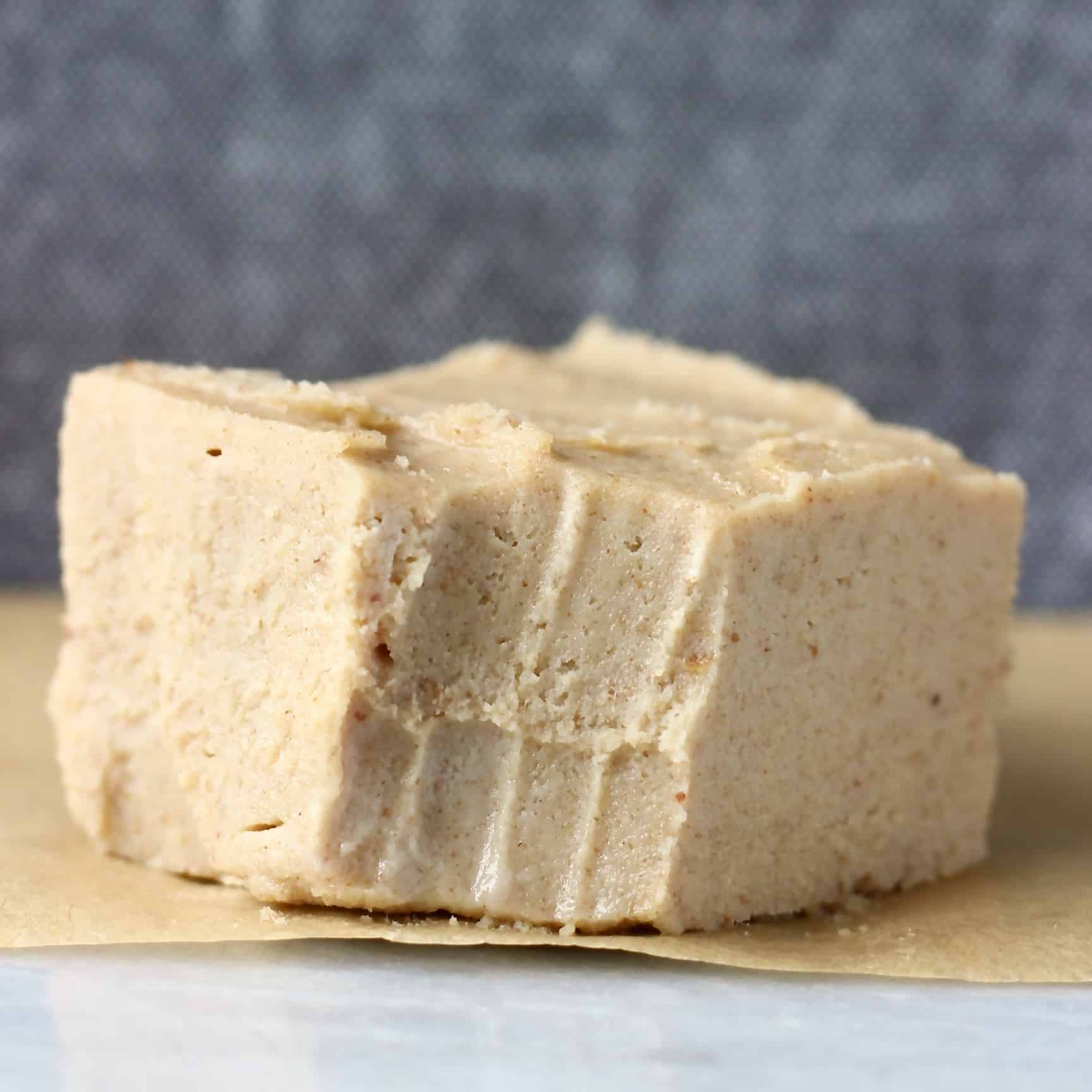 Photo of a square of caramel-coloured fudge with a bite taken out of it on a marble slab against a dark grey background