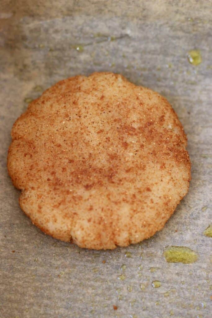 Photo of a raw white cookie coated in brown cinnamon sugar against a sheet of brown baking paper