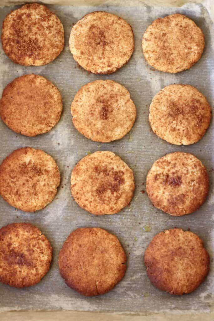 Photo of twelve cookies coated in brown cinnamon sugar on a sheet of brown baking paper