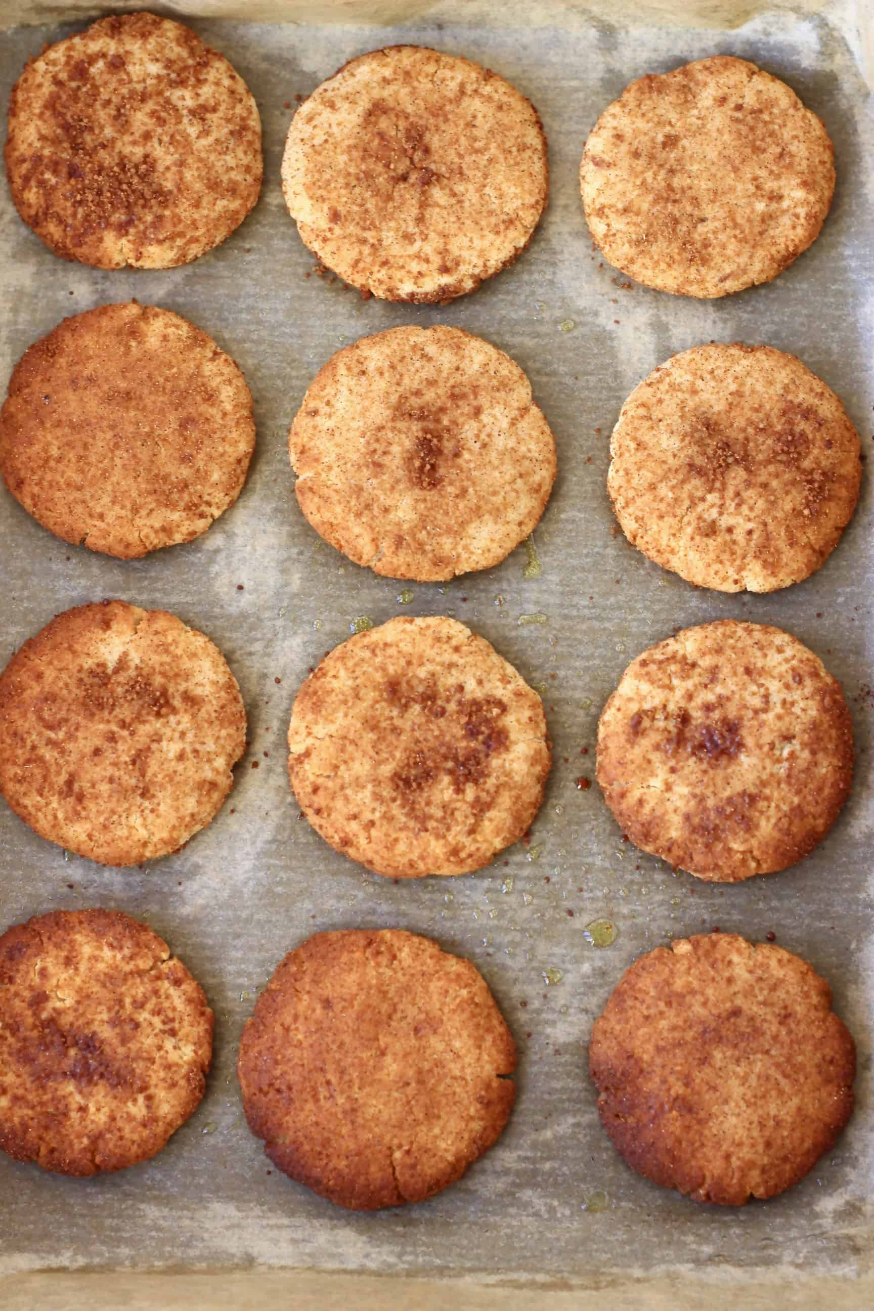 Twelve gluten-free vegan snickerdoodles on a baking tray lined with baking paper