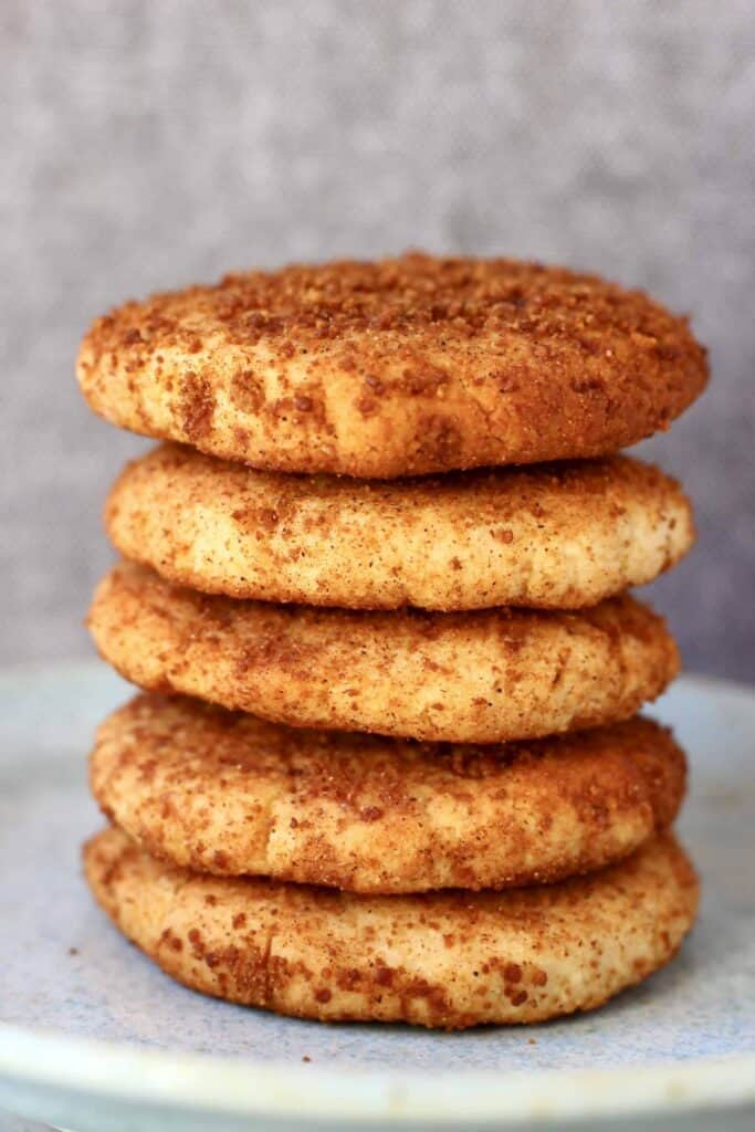 Photo of five cookies coated in brown cinnamon sugar stacked on top of each other on a light blue plate against a grey background
