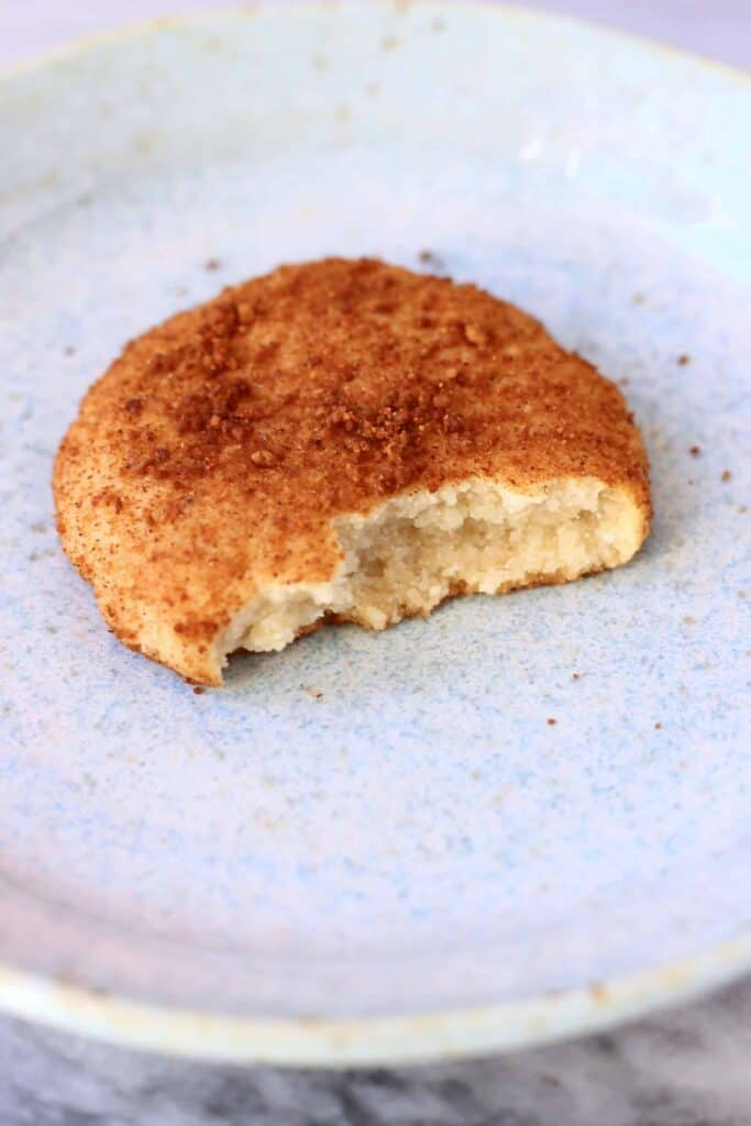 Photo of a white cookie coated in brown cinnamon sugar with a bite taken out of it on a light blue plate