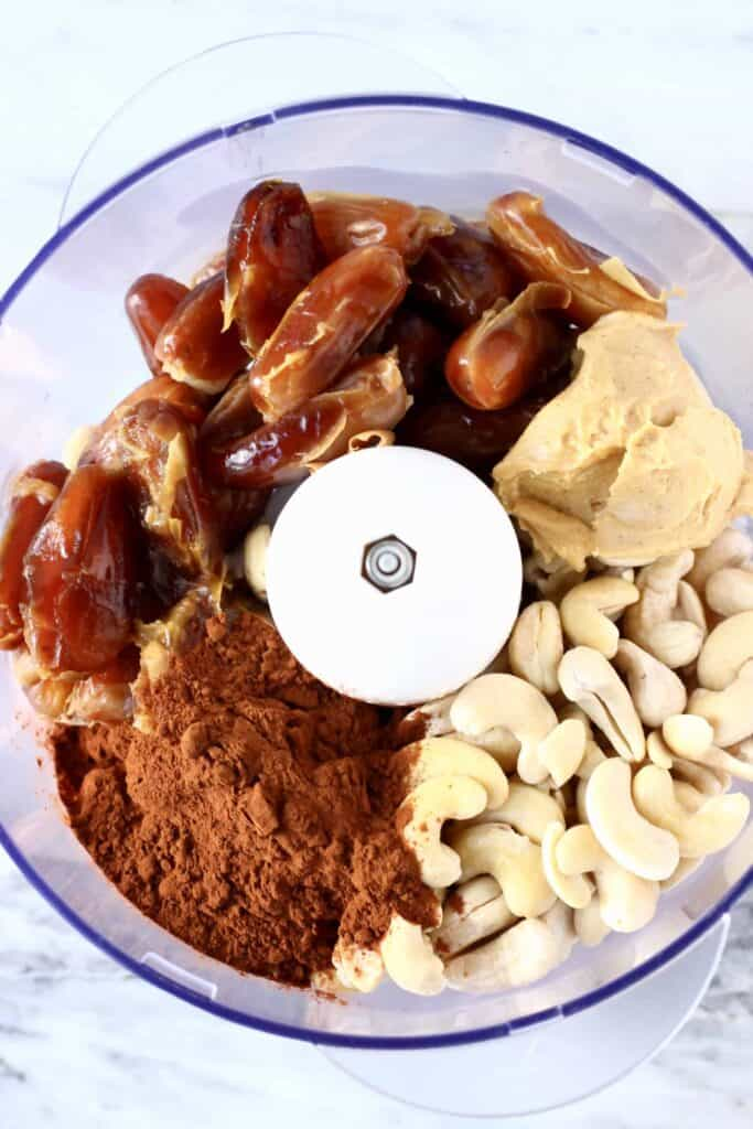 Photo of cocoa powder, cashew nuts, dates and almond butter in a food processor