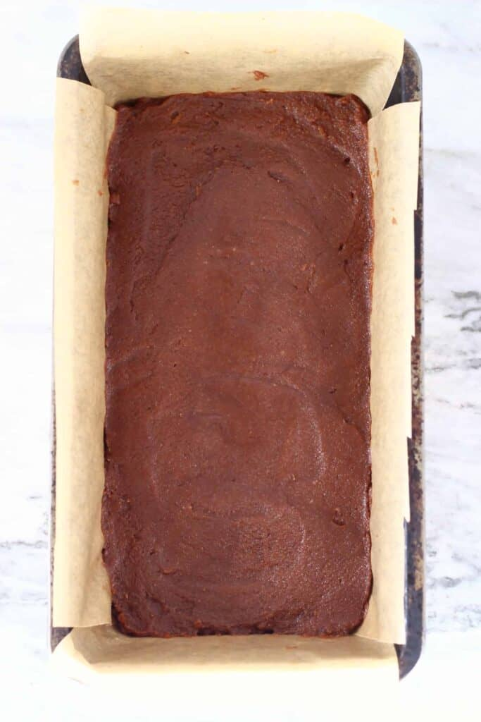 Photo of chocolate fudge mixture in a black loaf tin lined with brown baking paper