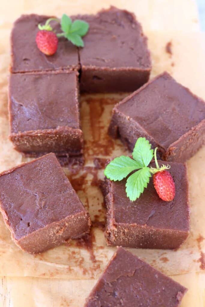 Photo of seven square pieces of chocolate fudge on a sheet of brown baking paper decorated with mini strawberries with green leaves