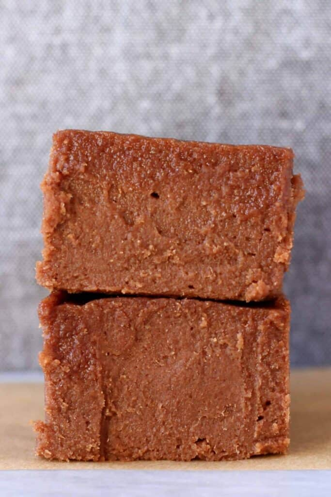 Photo of two squares of chocolate fudge on a sheet of brown baking paper against a grey background
