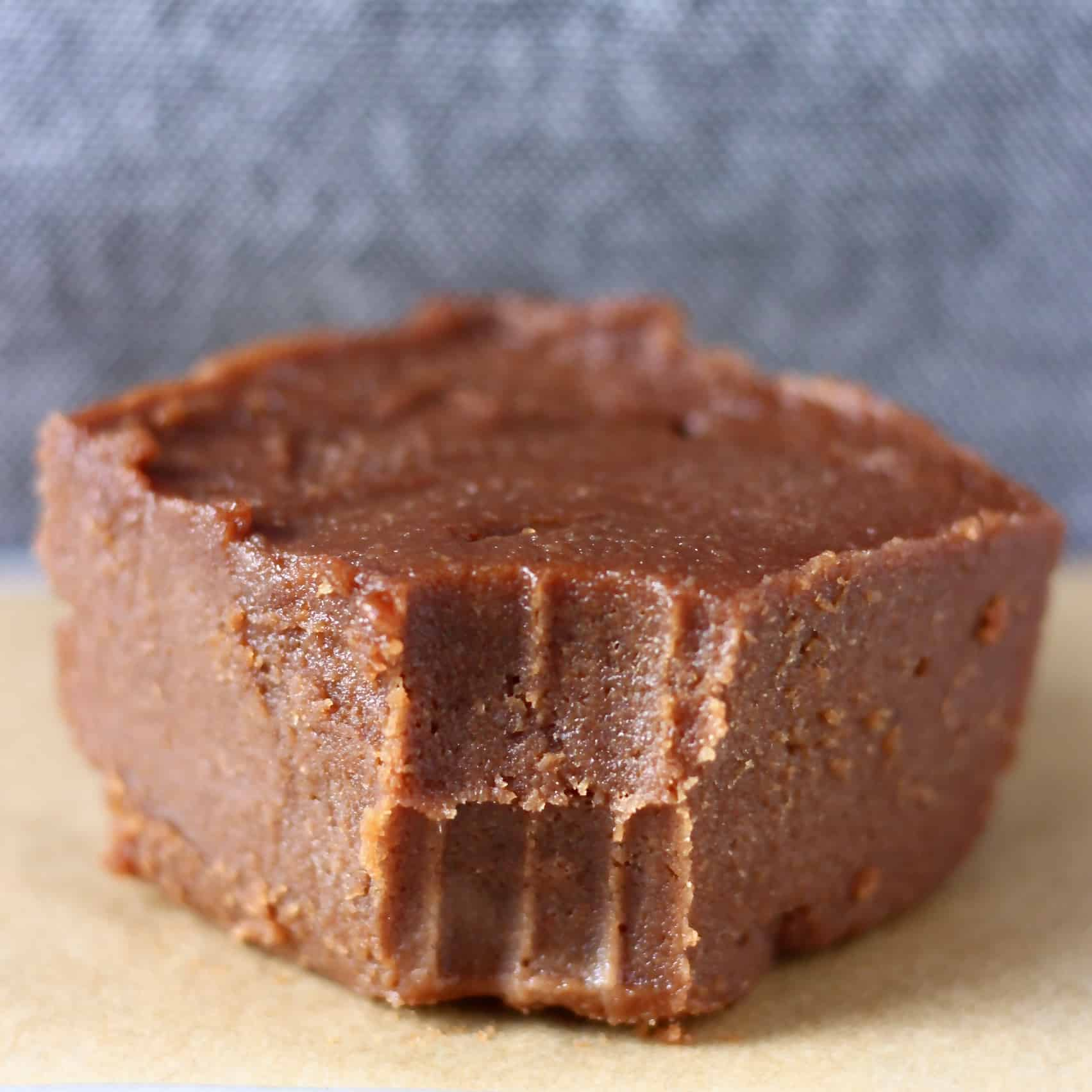 Photo of a square of chocolate fudge with a bite taken out of it on a piece of brown baking paper against a grey background