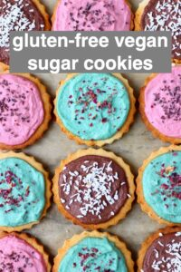 Photo of twelve circular cookies topped with different coloured frosting and sprinkles on a sheet of brown baking paper