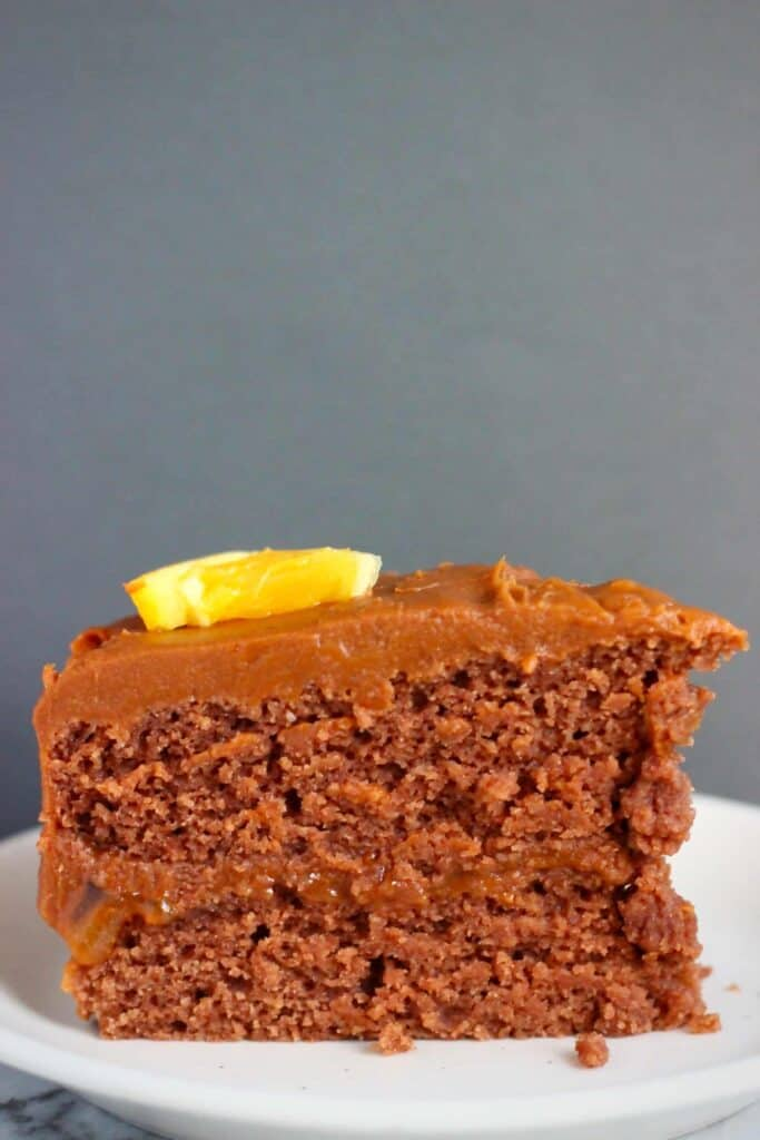 Photo of a slice of chocolate sponge sandwiched with chocolate frosting topped with a slice of orange against a dark grey background
