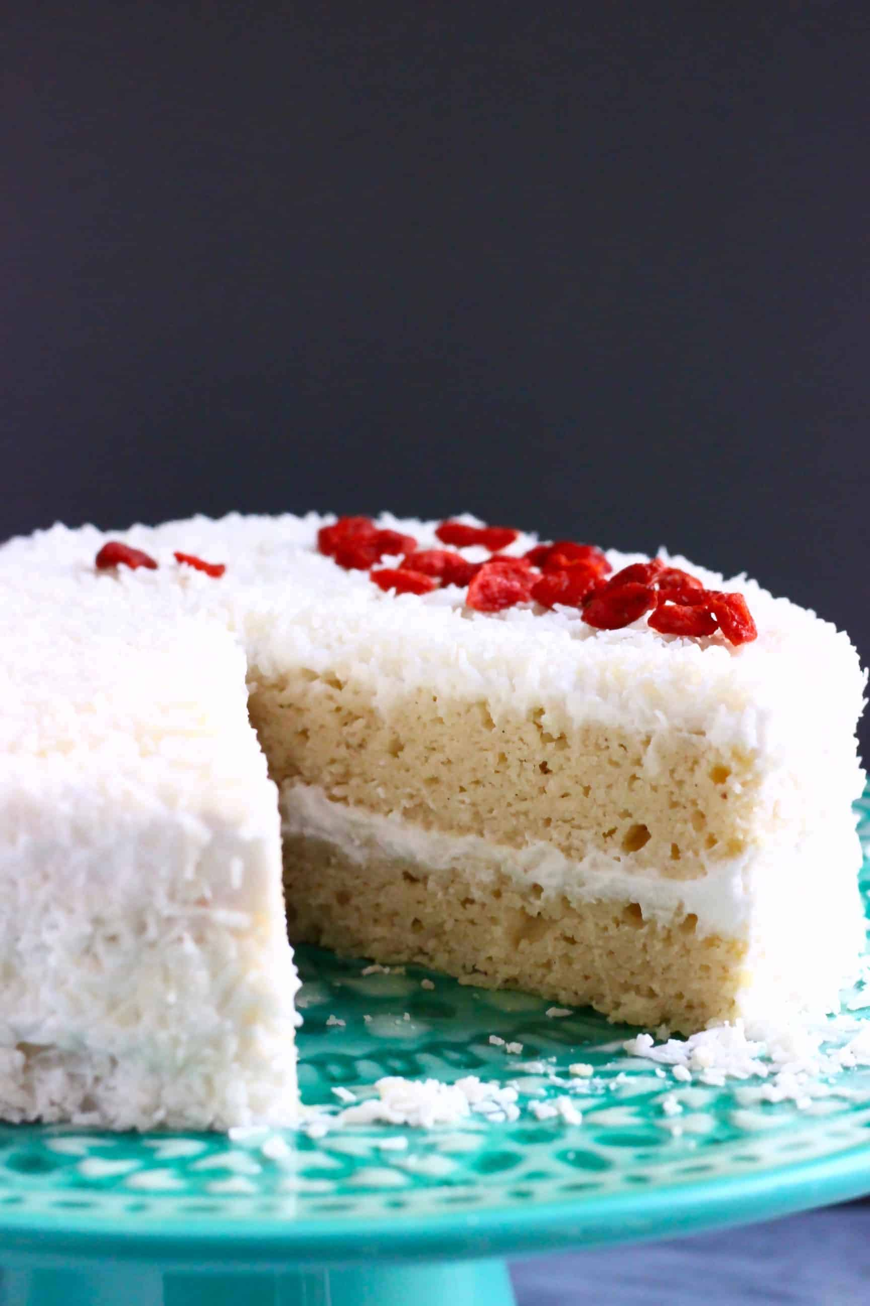 A white coconut cake covered in creamy frosting and coconut sprinkled with red goji berries against a dark grey background