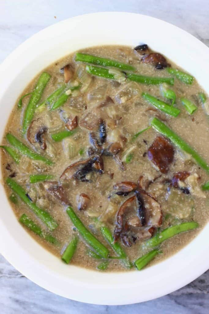 Photo of brown creamy mushroom soup and green beans in a white pie dish against a marble background