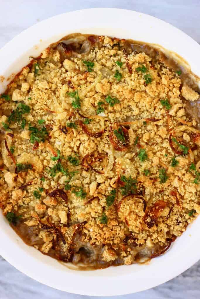Photo of green bean casserole topped with golden brown breadcrumbs and green parsley in a white pie dish against a marble background