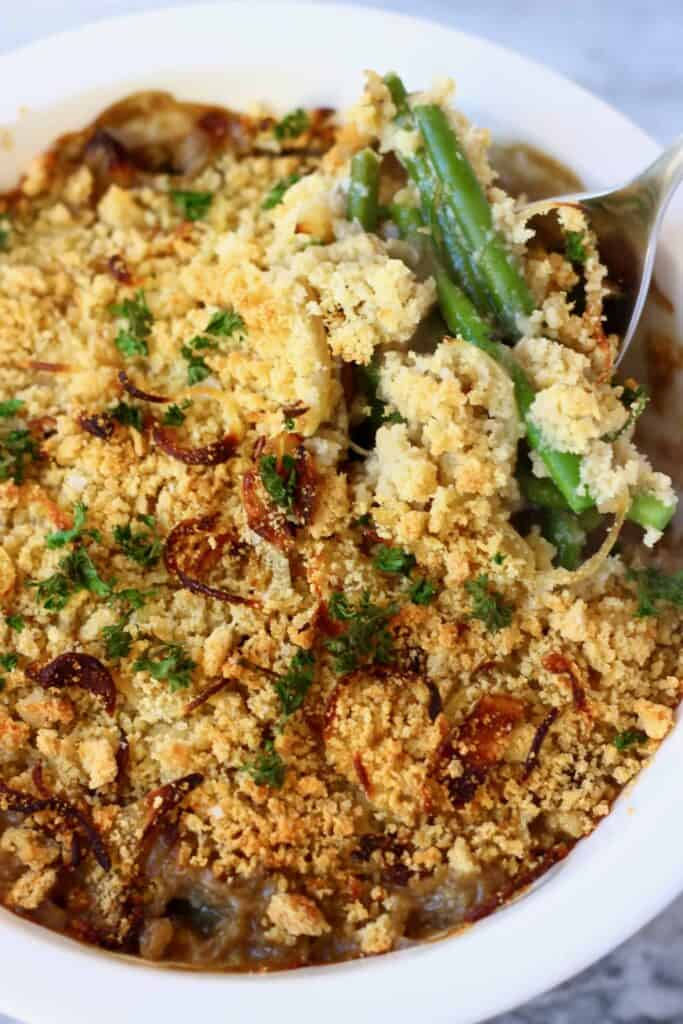 Photo of green bean casserole topped with brown breadcrumbs and crispy onions with a spoon lifting up a few green beans