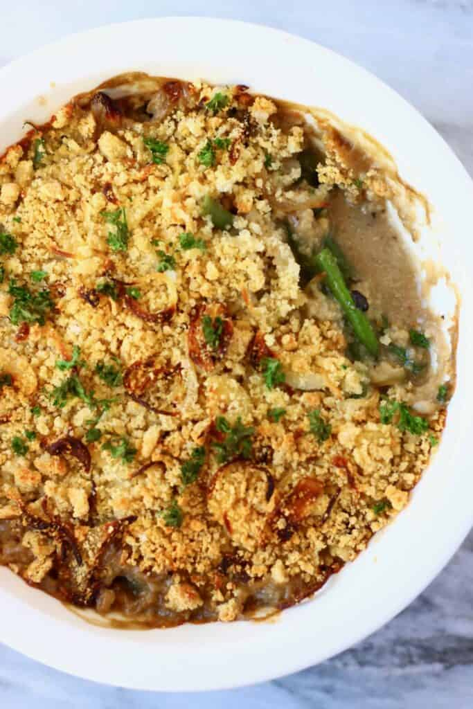 Photo of green bean casserole topped with golden brown breadcrumbs and green parsley in a white pie dish with a mouthful taken out of it against a marble background