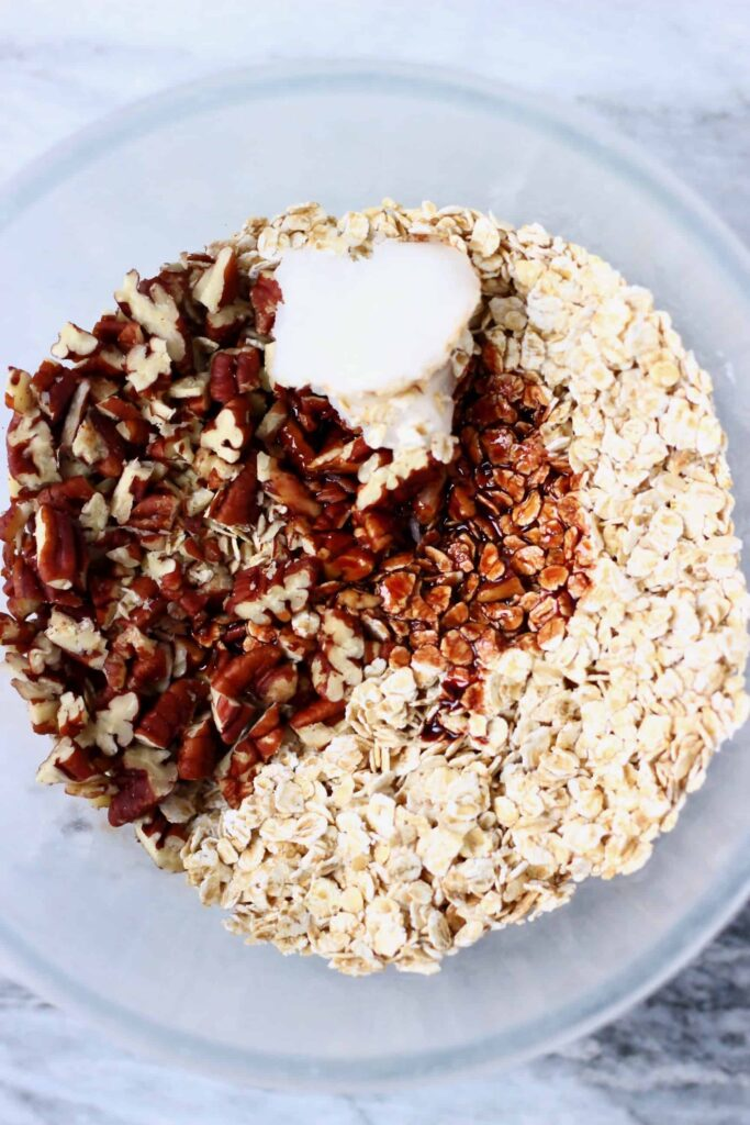 Photo of chopped pecan nuts, coconut oil and oats in a glass mixing bowl against a marble background
