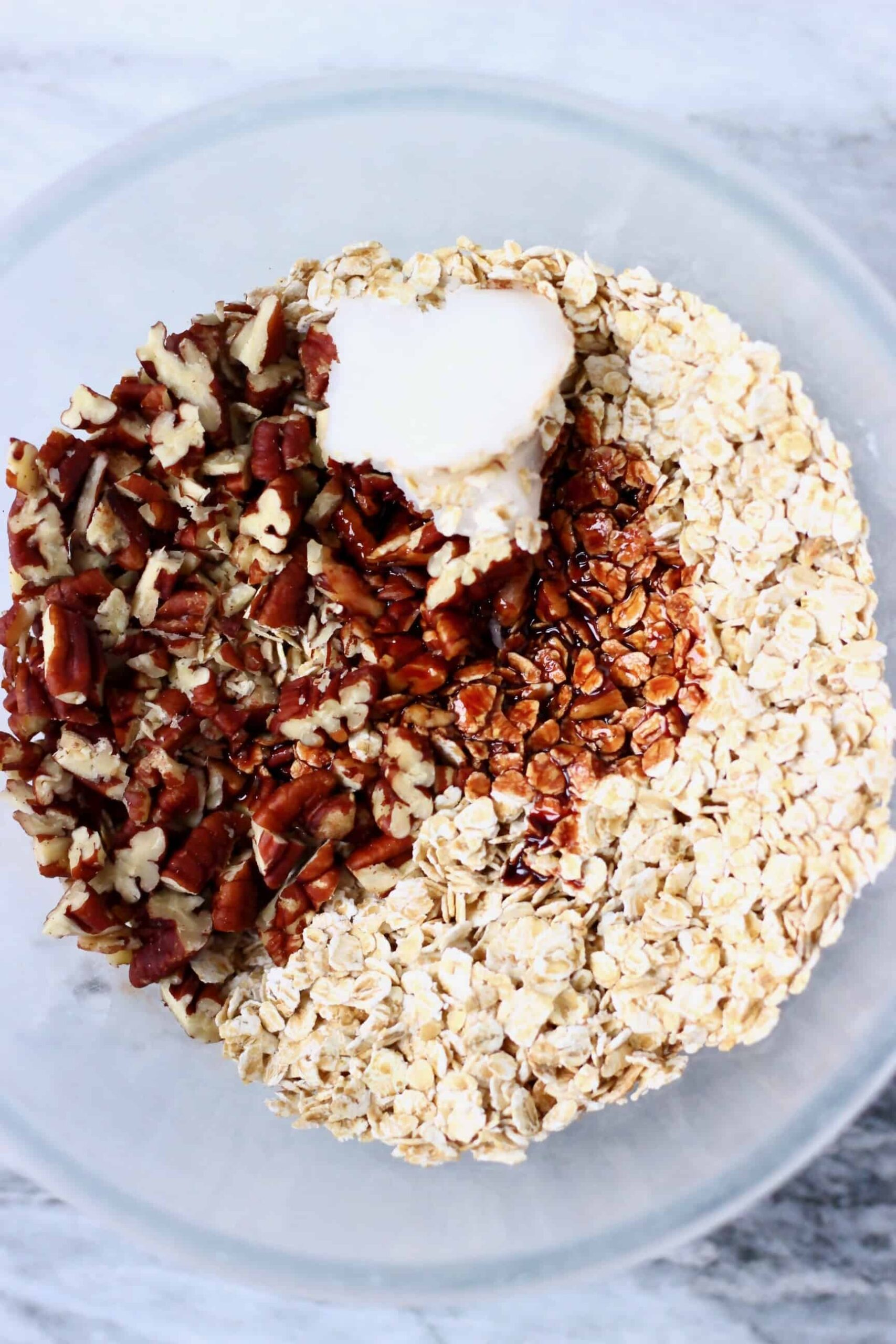 Chopped pecan nuts, coconut oil and oats in a mixing bowl