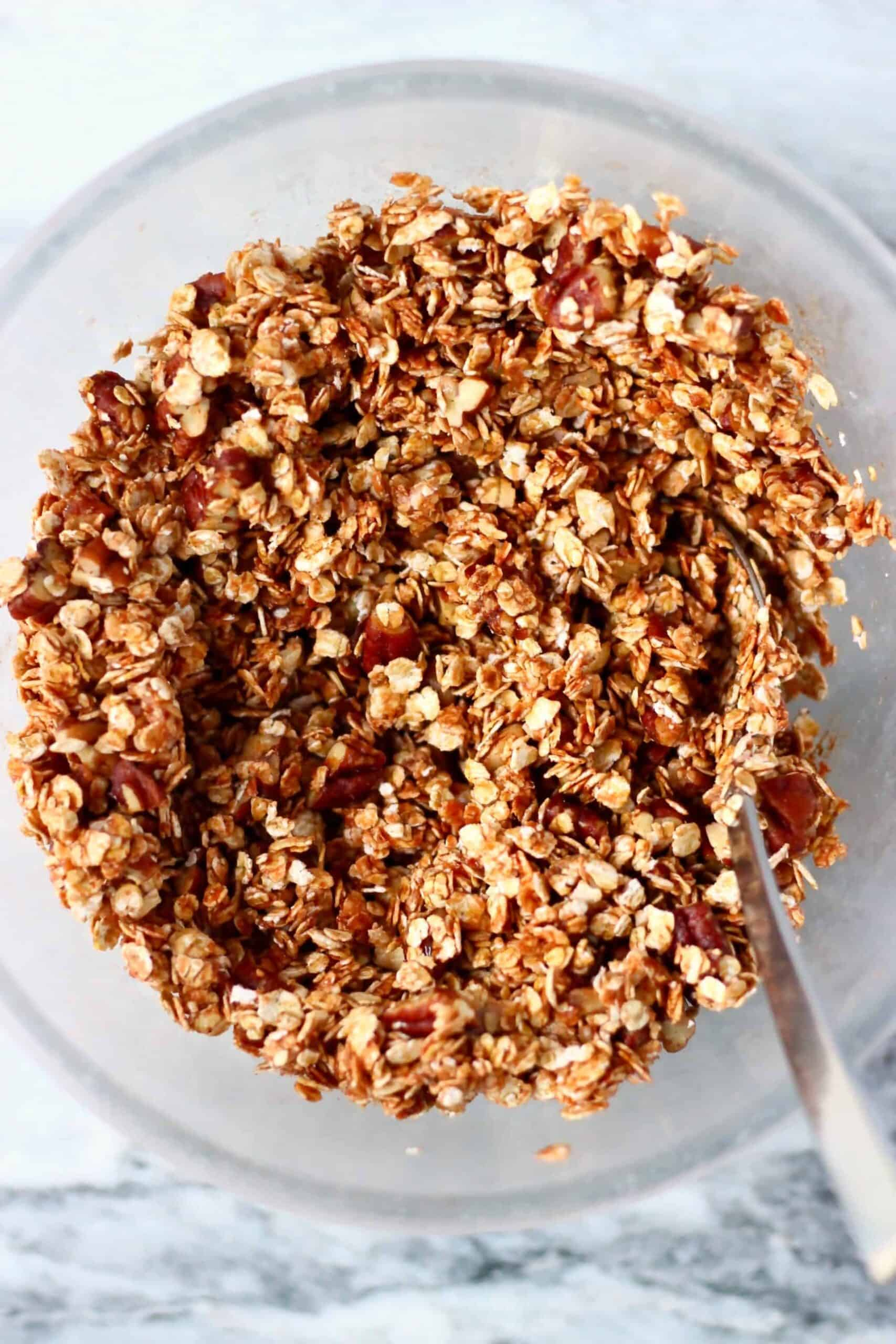 Oats, pecan nuts and syrup mixed together in a bowl