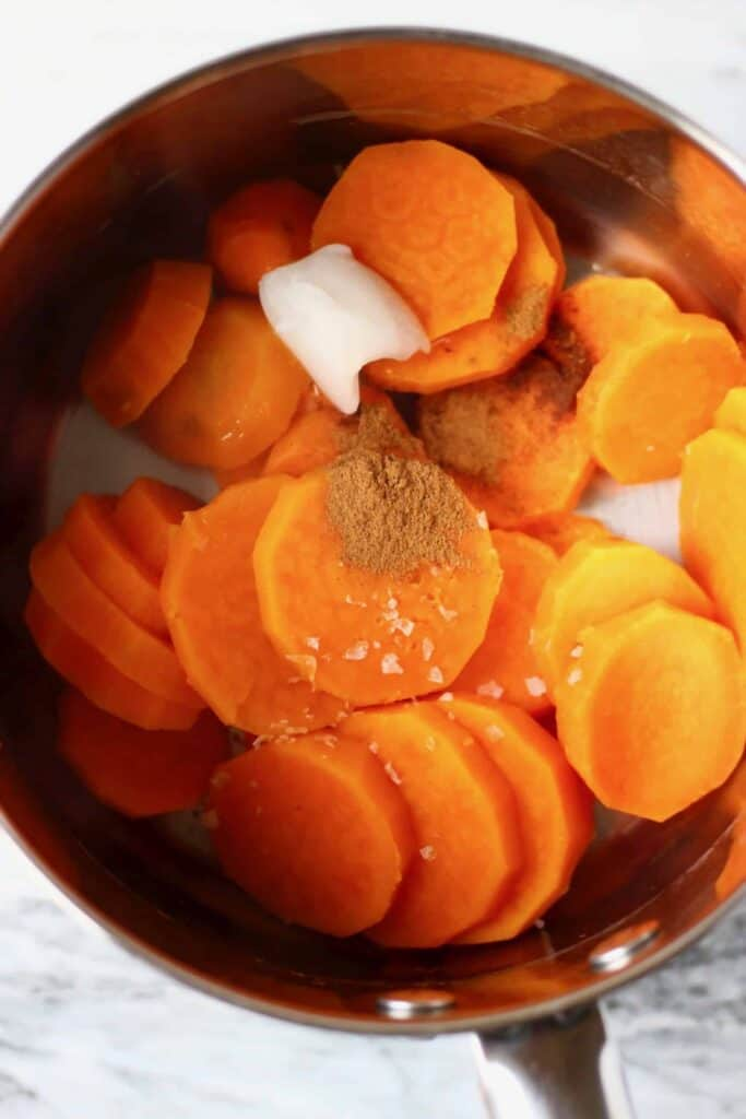 Cooked sweet potatoes, coconut oil and brown spices in a silver pan against a marble background