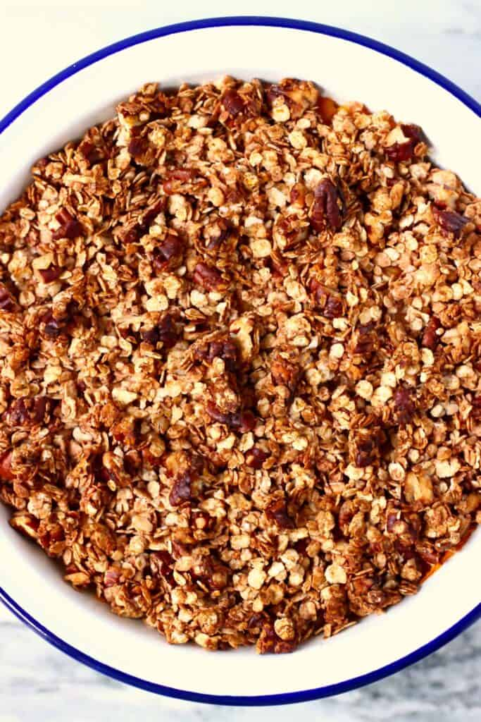 Photo of chopped pecans and oats in a white pie dish with a blue rim against a marble background