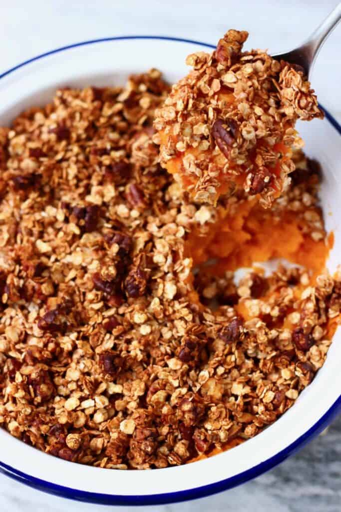 Photo of mashed sweet potatoes topped with chopped pecan nuts and oatmeal with a silver spoon lifting up a mouthful of it