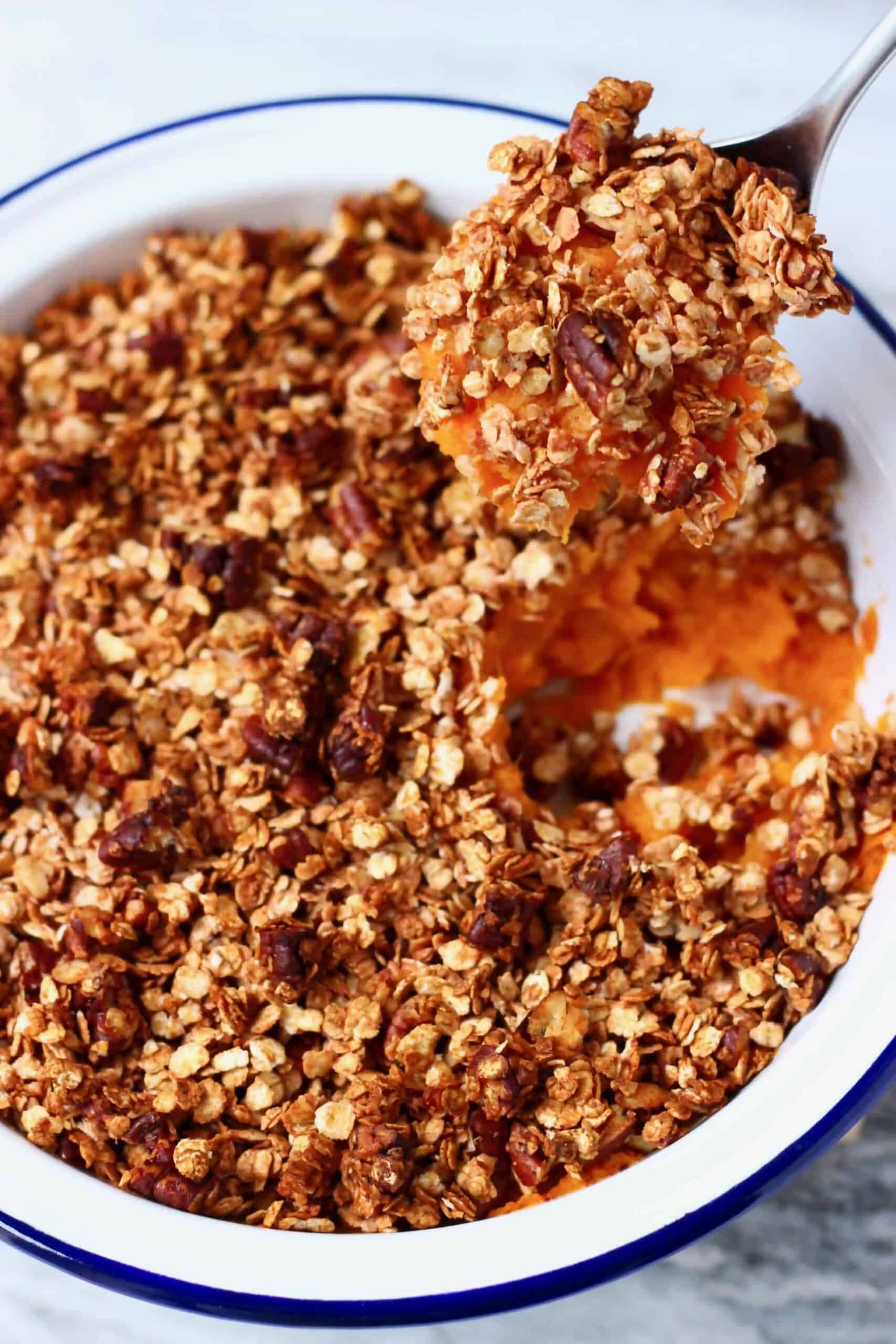 Vegan sweet potato casserole in a pie dish with a spoon lifting up a mouthful