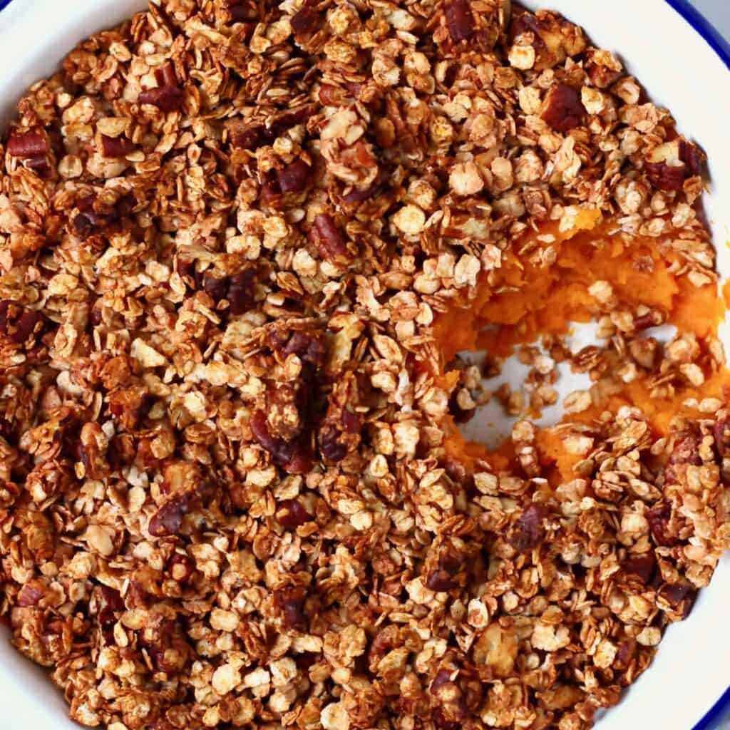 Photo of mashed sweet potatoes topped with chopped pecans and oats in a white pie dish with a mouthful taken out of it