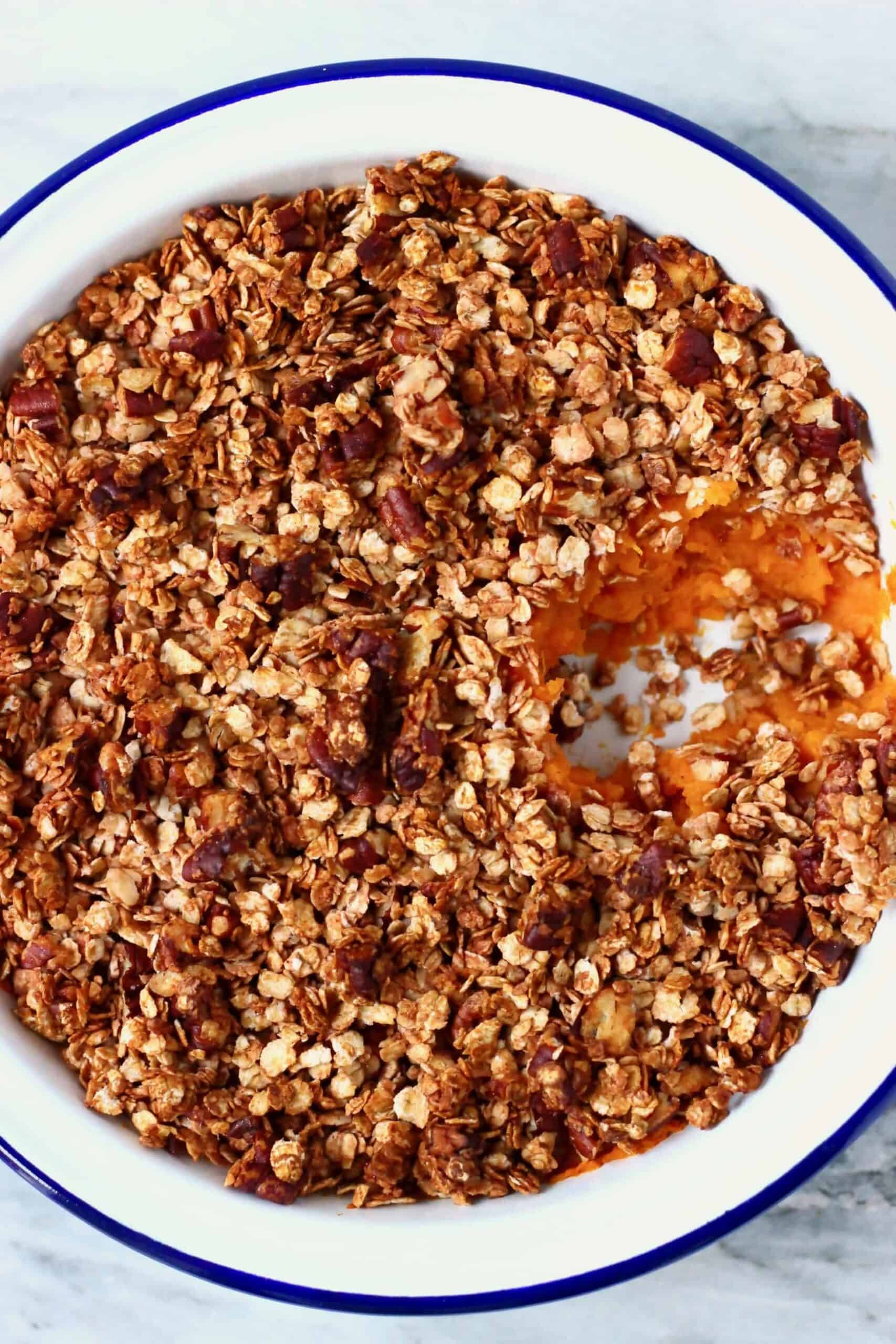 Vegan sweet potato casserole in a pie dish with a mouthful taken out of it