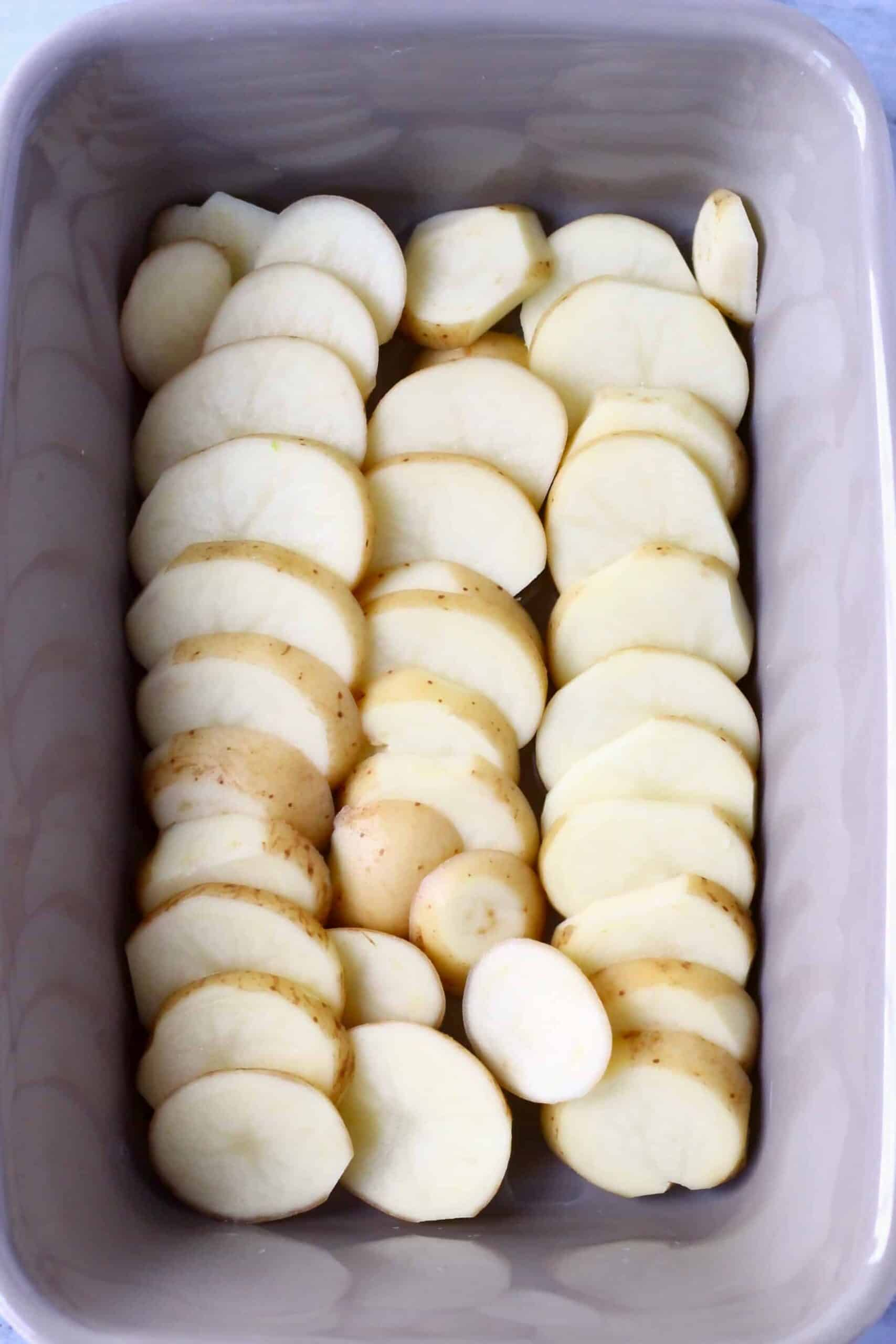 Sliced potatoes in a rectangular baking dish