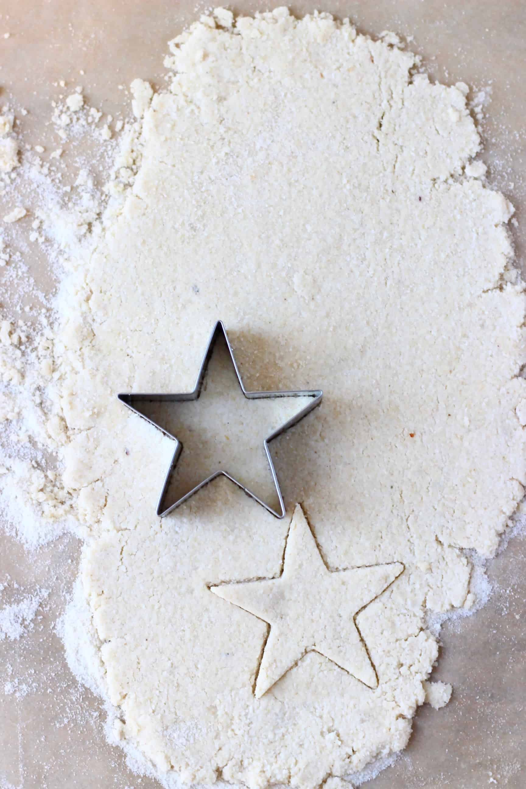Gluten-free vegan pastry dough rolled out on a sheet of baking paper with a star-shaped cookie cutter on it