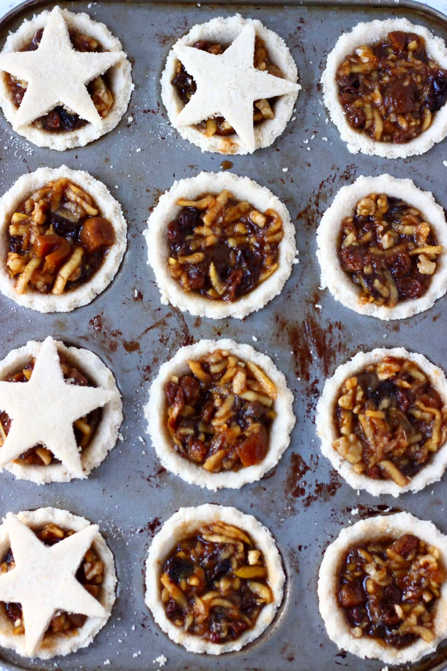 Twelve gluten-free vegan mince pies pastry crusts in a muffin tin filled with vegan mincemeat