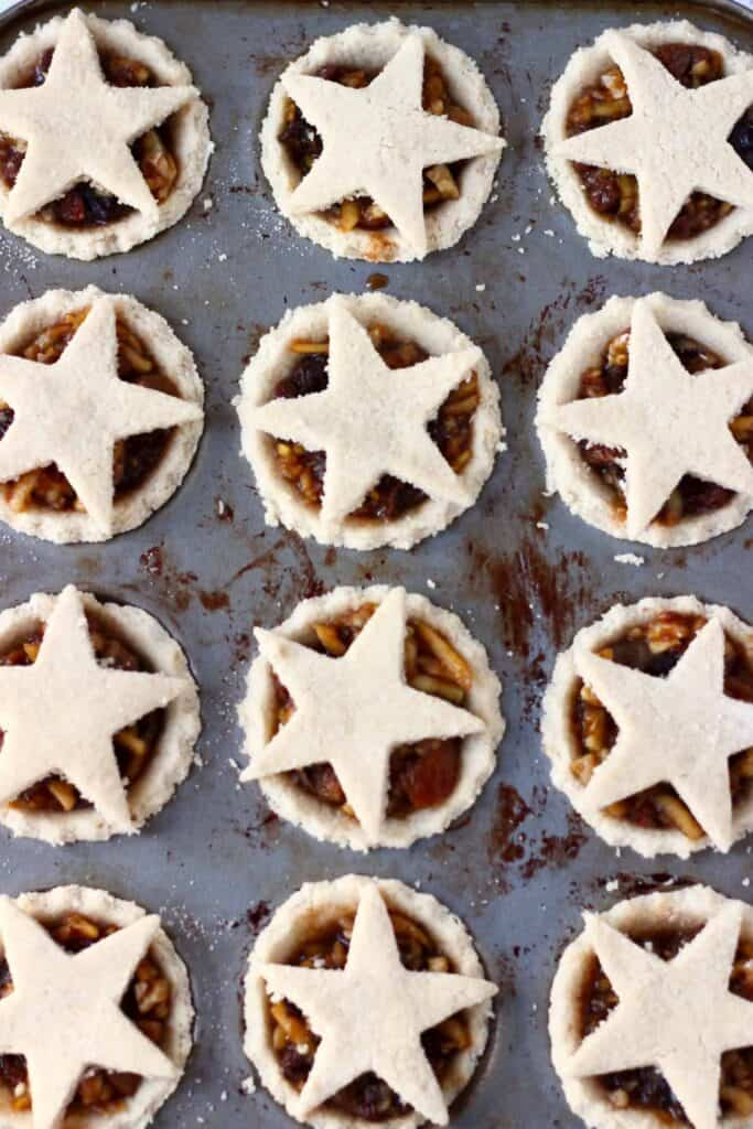 Photo of 12 mini pie pastry crusts filled with dried fruit and topped with a pastry star in a silver tart tin