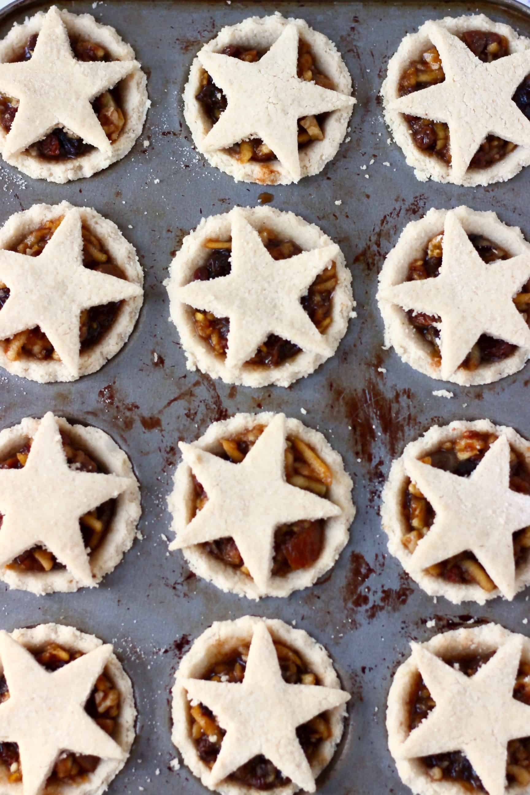Twelve raw gluten-free vegan mince pies pastry crusts in a muffin tin filled with vegan mincemeat and topped with pastry stars