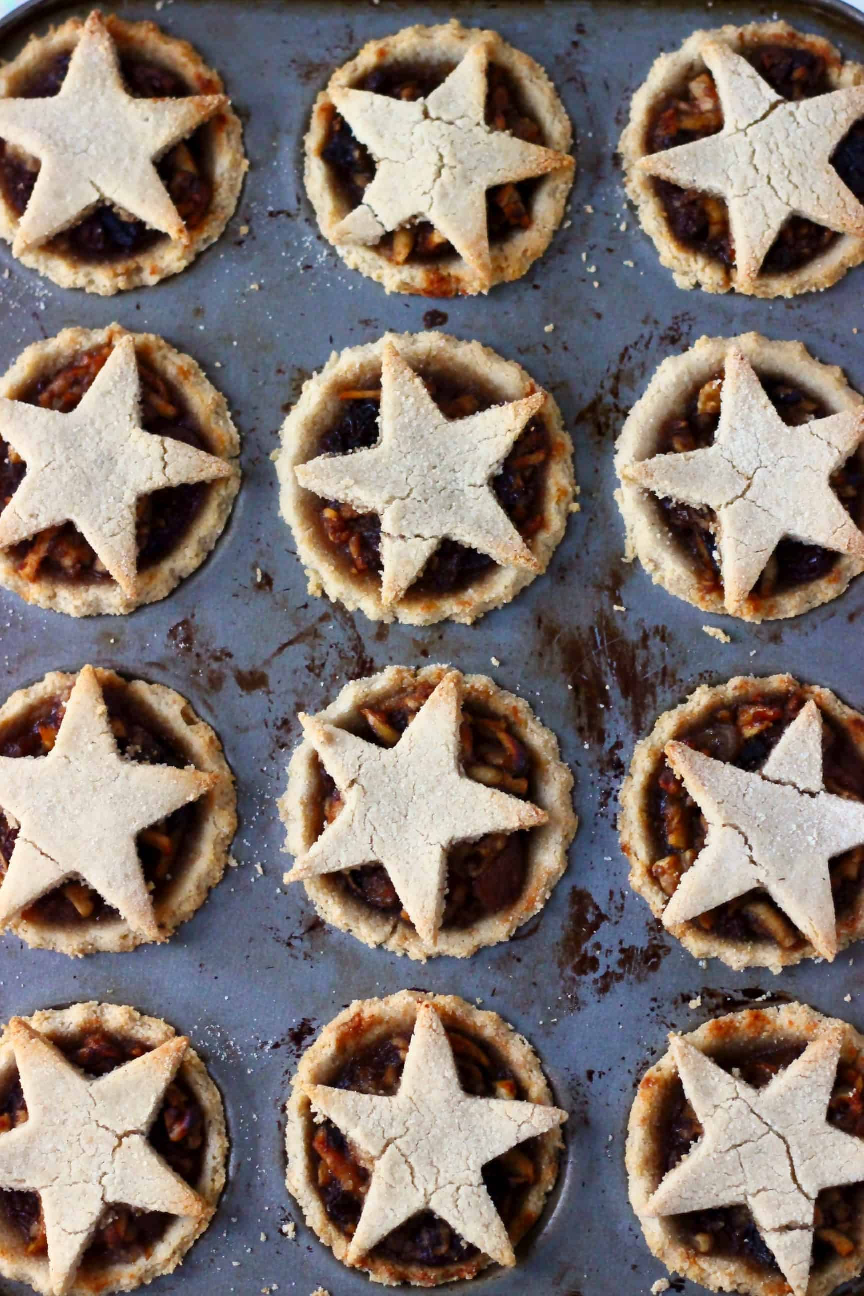 Twelve gluten-free vegan mince pies in a muffin tin topped with pastry stars