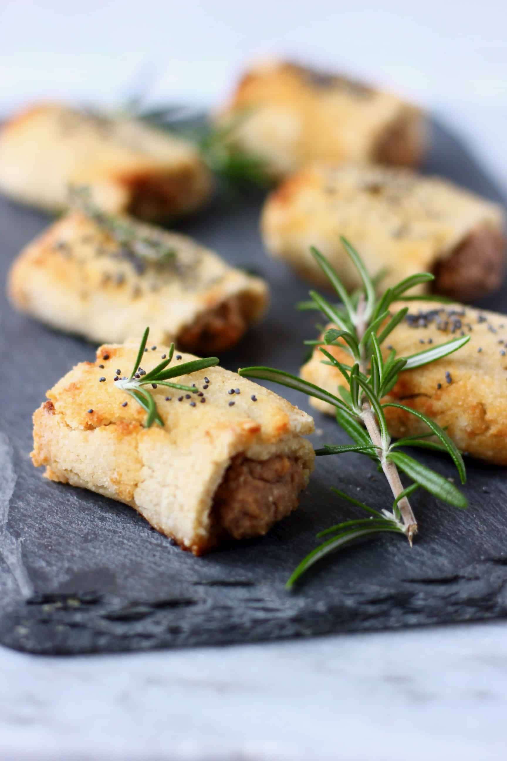 Six vegan sausage rolls sprinkled with poppy seeds on a black slab decorated with sprigs of rosemary